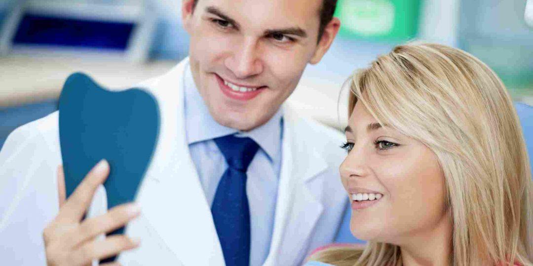 dentist and patient looking in handheld mirror